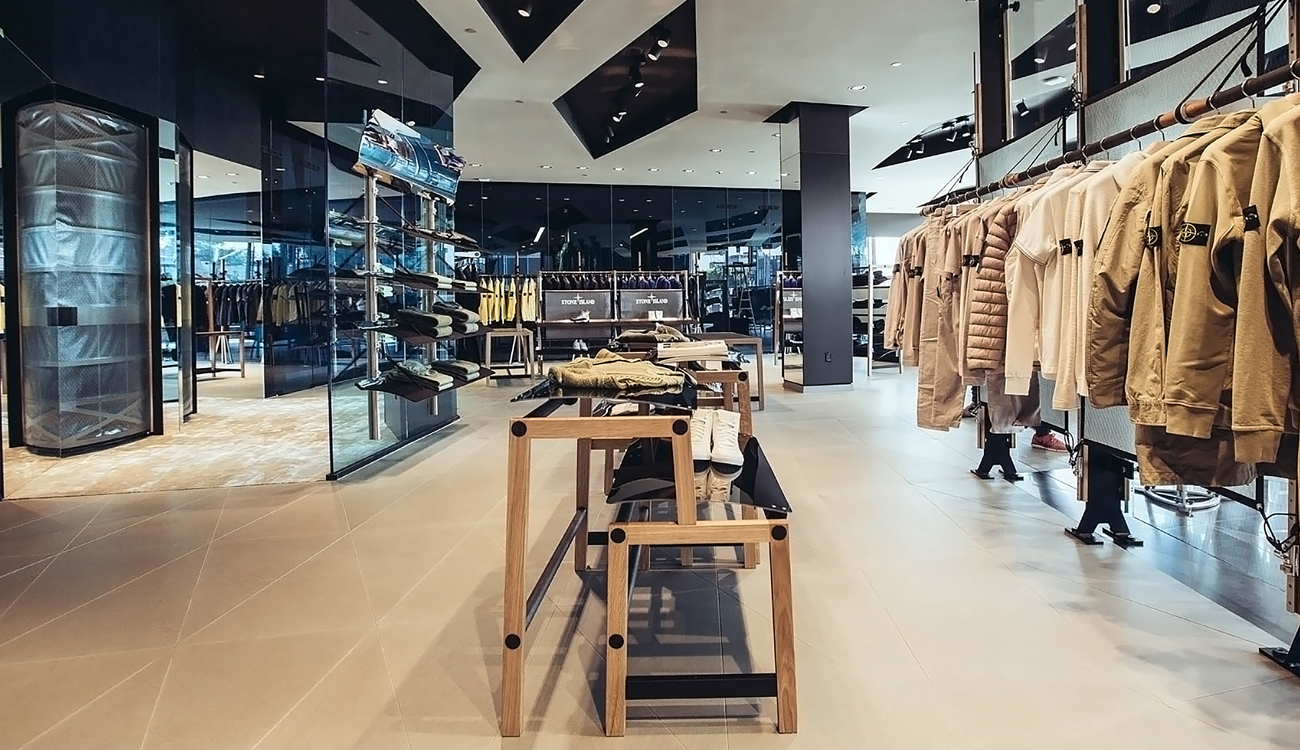 Store interior with mirrored wall, glass panels, white ceiling and floor, black ceiling spotlights and merchandise displayed throughout.
