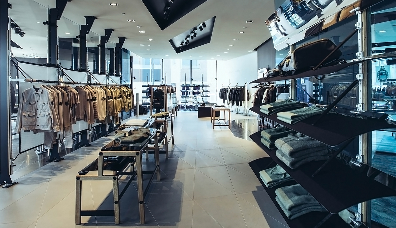 Contemporary, brightly lit store with a rack of clothes in beige organized by shade and other clothes on shelves and display tables.