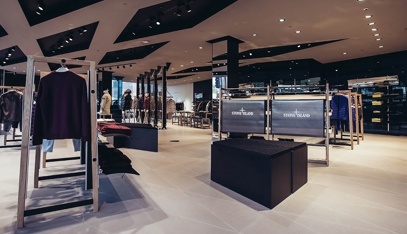 Contemporary store interior with a white and black ceiling, white stone floor tiles, black ceiling spotlights and contemporary store fittings.