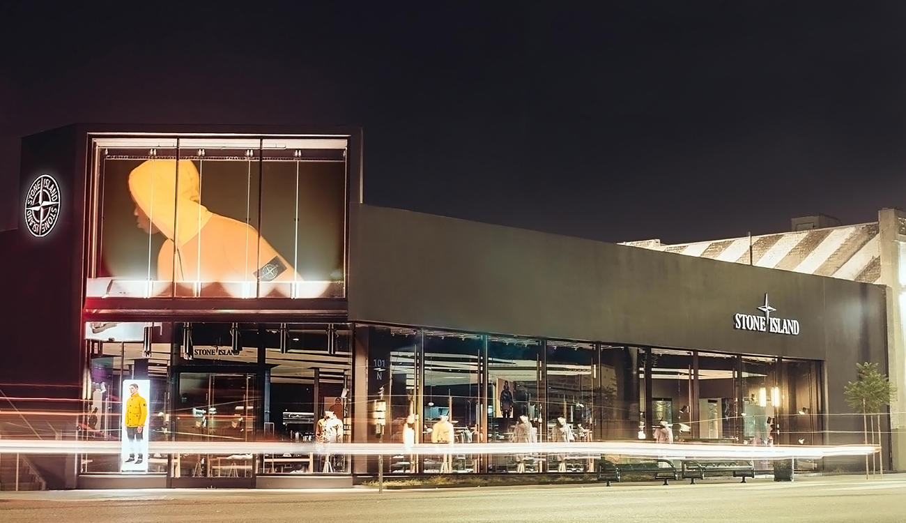 Street view of storefront lit up at night showing large billboard of model in an orange Stone Island jacket over the entrance.