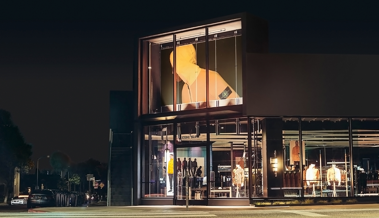 Street view of storefront lit up at night with large billboard of model in an orange Stone Island jacket over the entrance.