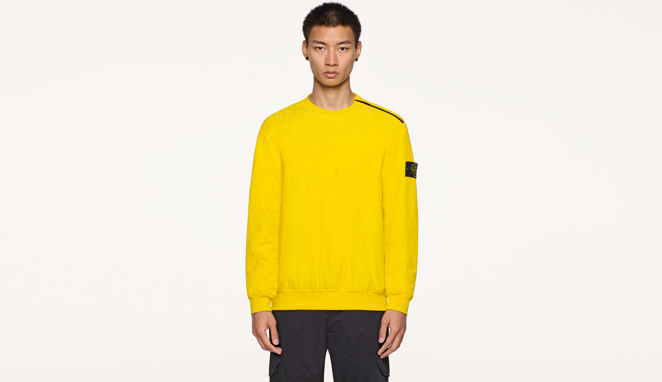 Model wearing yellow, performance crewneck top with Stone Island badge on left arm.