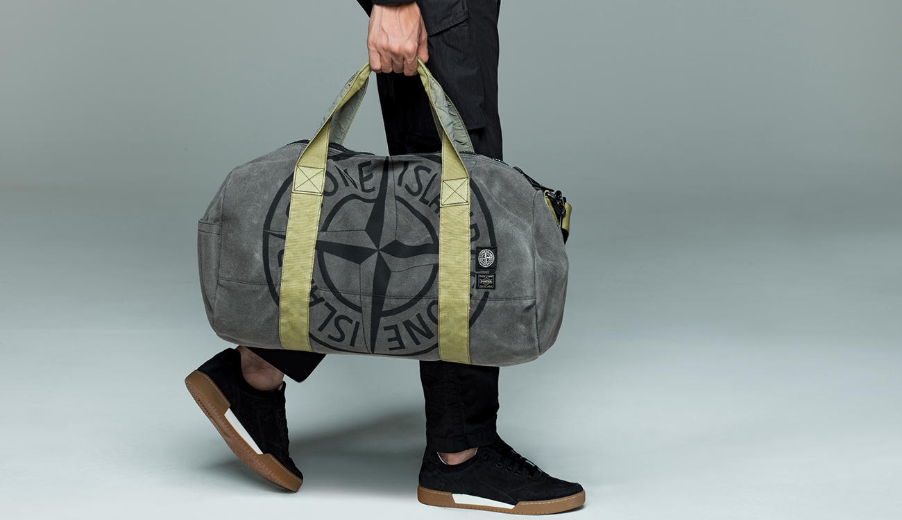 Model holding gray duffle bag in Man Made Suede TC with nylon green handles.