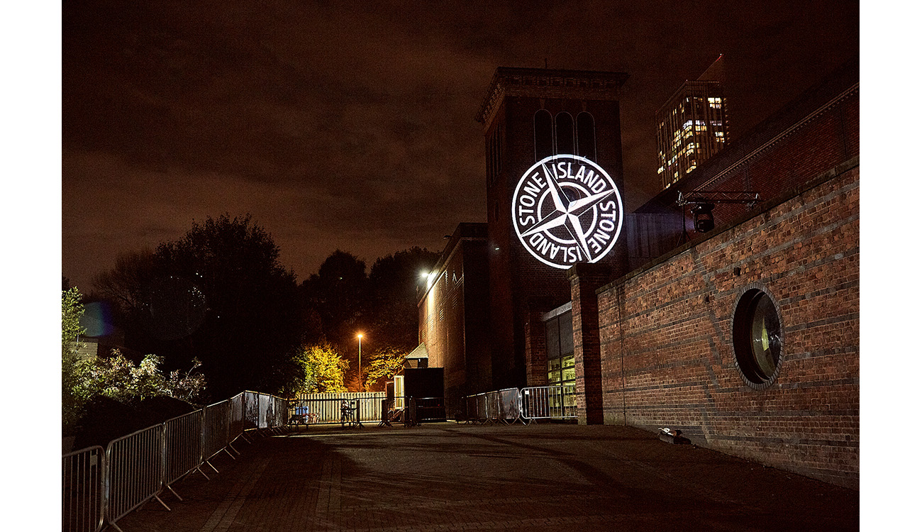 Exterior shot of building at night with the white Stone Island compass logo projected on the wall.