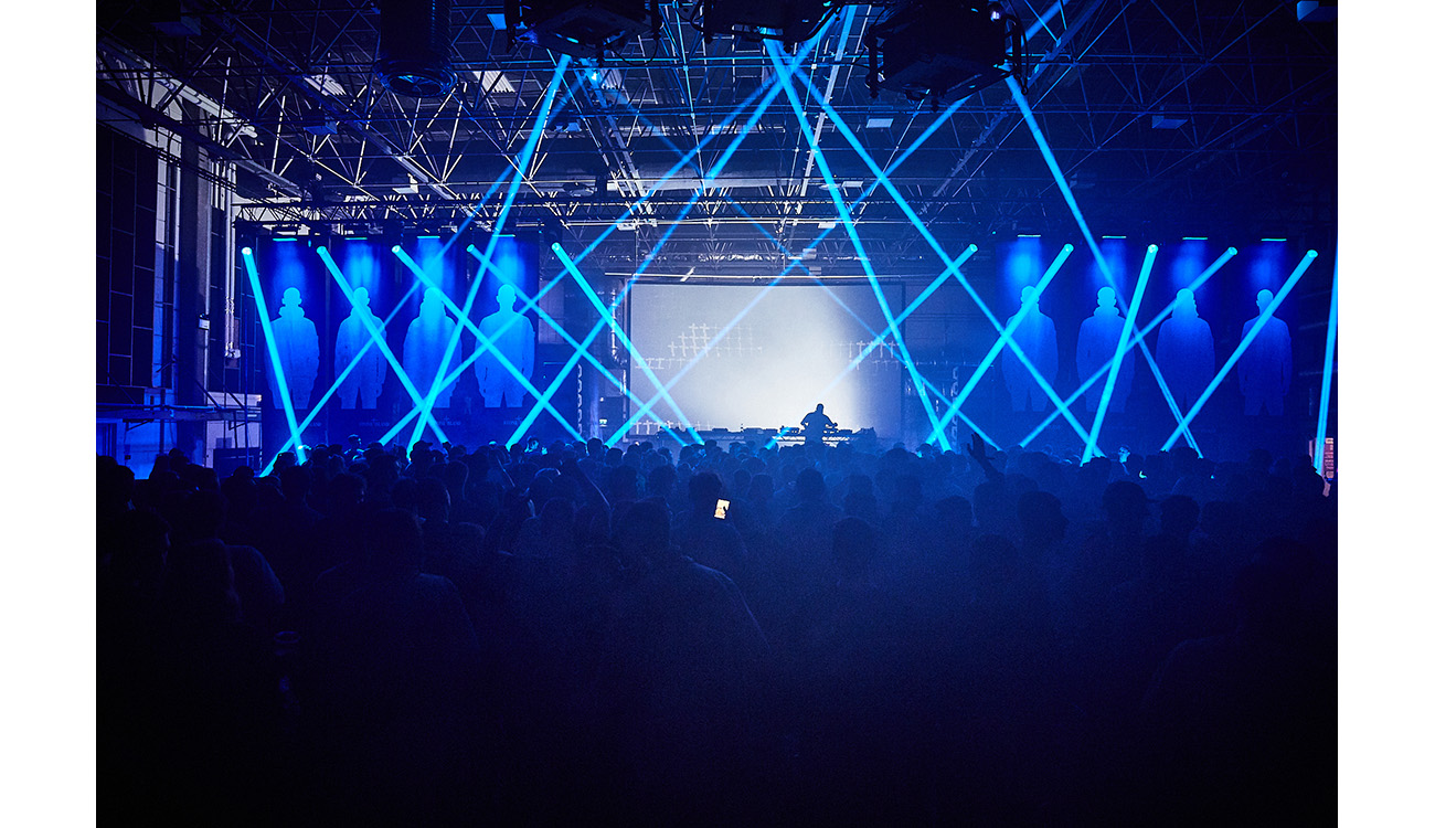 Wide view of club with blue laser lights, the DJ table, a large screen and lots of people.
