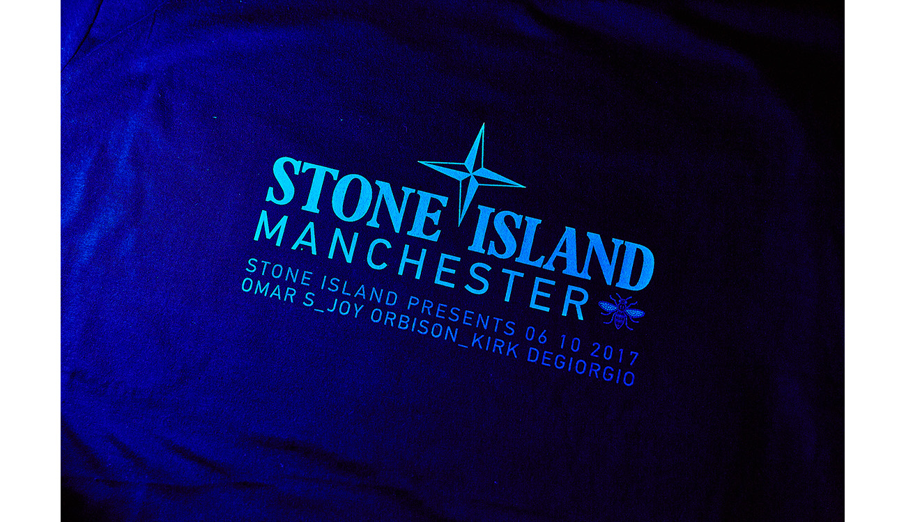 Close up of Stone Island Manchester motif printed on blue fabric.