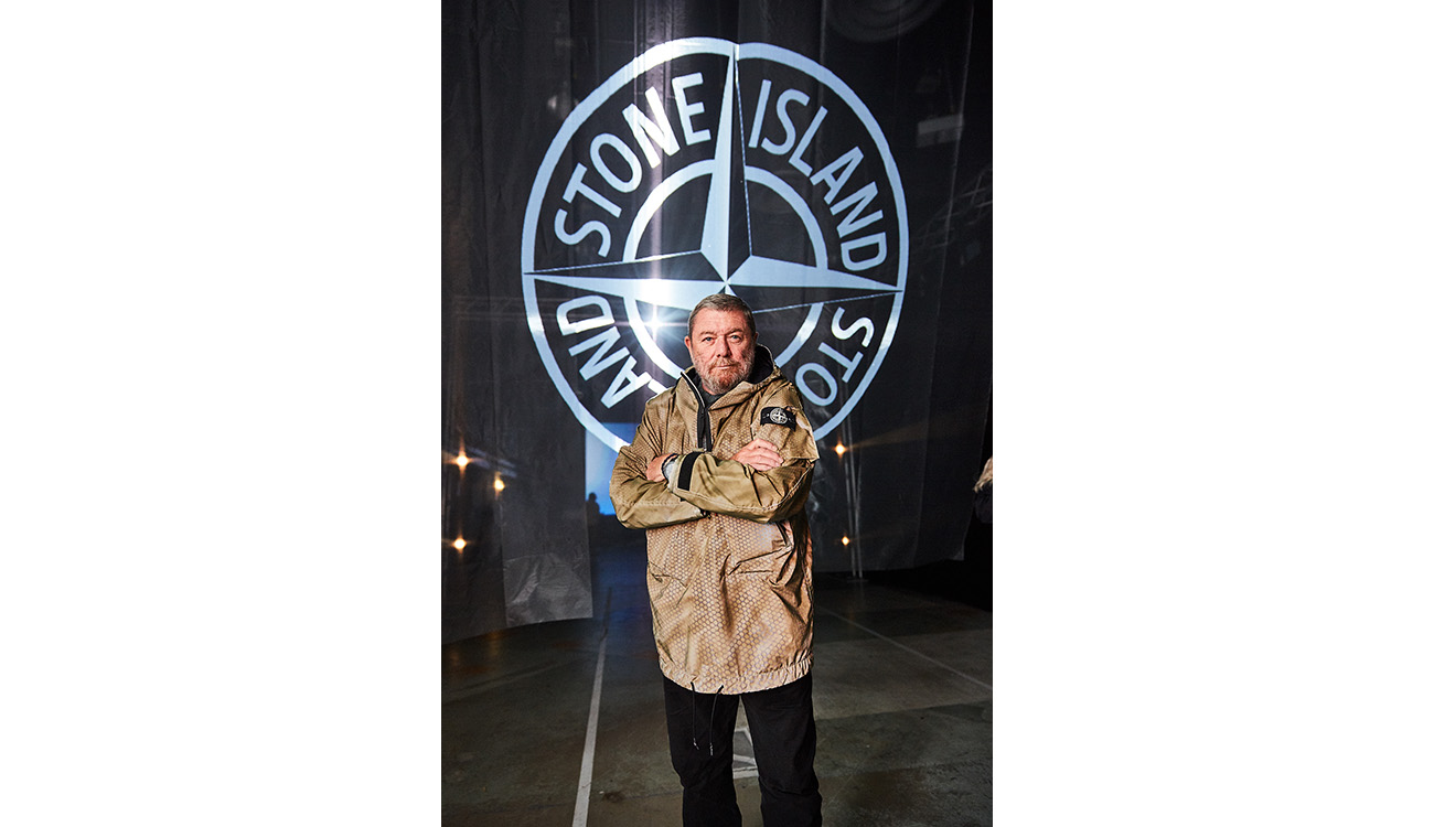 CEO of Stone Island Carlo Rivetti standing under a large Stone Island compass logo, wearing a Prototype Research Series 1 anorak.