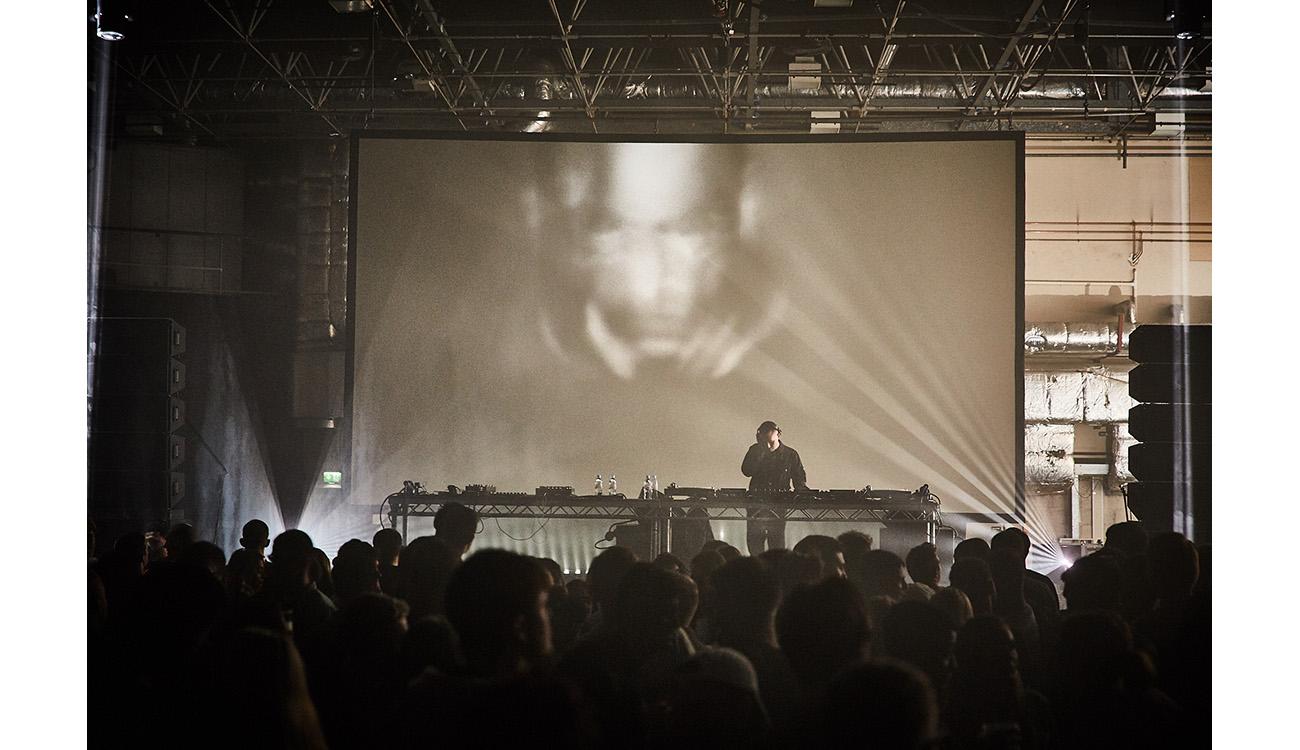 People watching DJ mixing behind large screen.