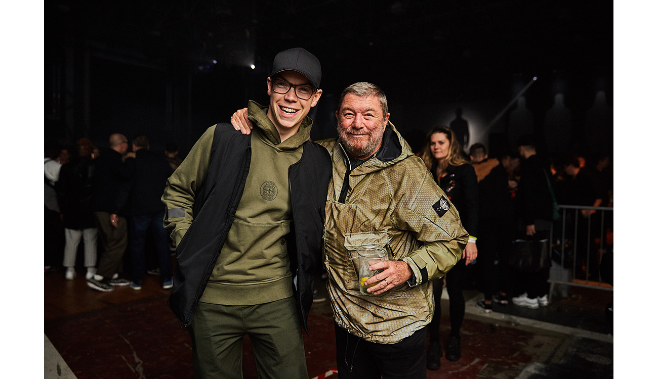 CEO of Stone Island Carlo Rivetti and another guy arm in arm and both wearing green Stone Island clothing.
