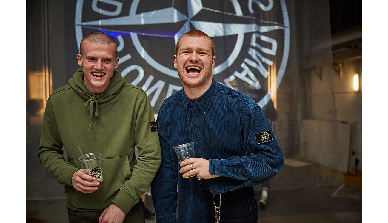 Two guys laughing, wearing Stone Island tops.