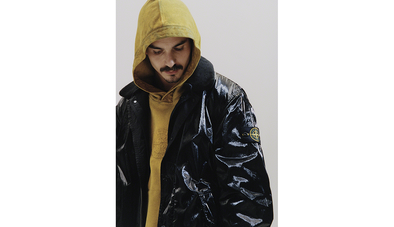Model wearing a black jacket in New Silk Light fabric over a yellow sweatshirt with Stone Island logo at chest.