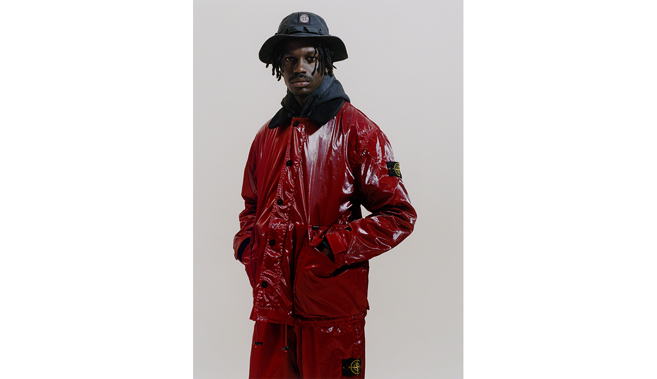 Model wearing a red jacket and red jogging pants both in New Silk Light fabric, and a blue boonie hat.