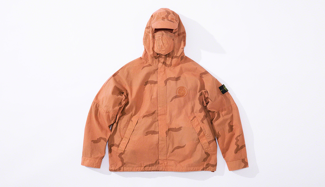 Orange jacket in brushed cotton canvas with a camouflage print, and a hood with visor and face guard, diagonal pockets and concealed closure.