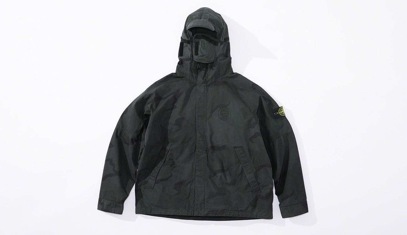 Black jacket in brushed cotton canvas with a camouflage print, and a hood with visor and face guard, diagonal pockets and concealed closure.