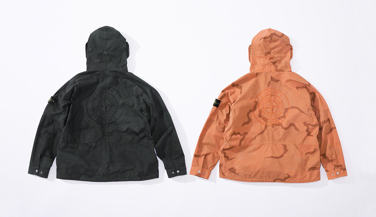Back of two jackets in brushed cotton canvas with a camouflage print, one black, one orange.