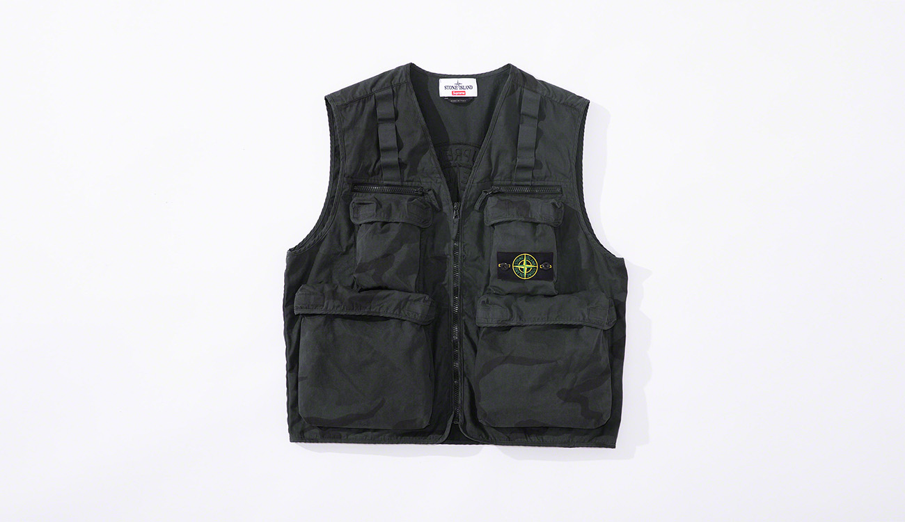 Black vest in brushed cotton canvas in a camouflage print, with multiple pockets and the Stone Island badge at left chest.