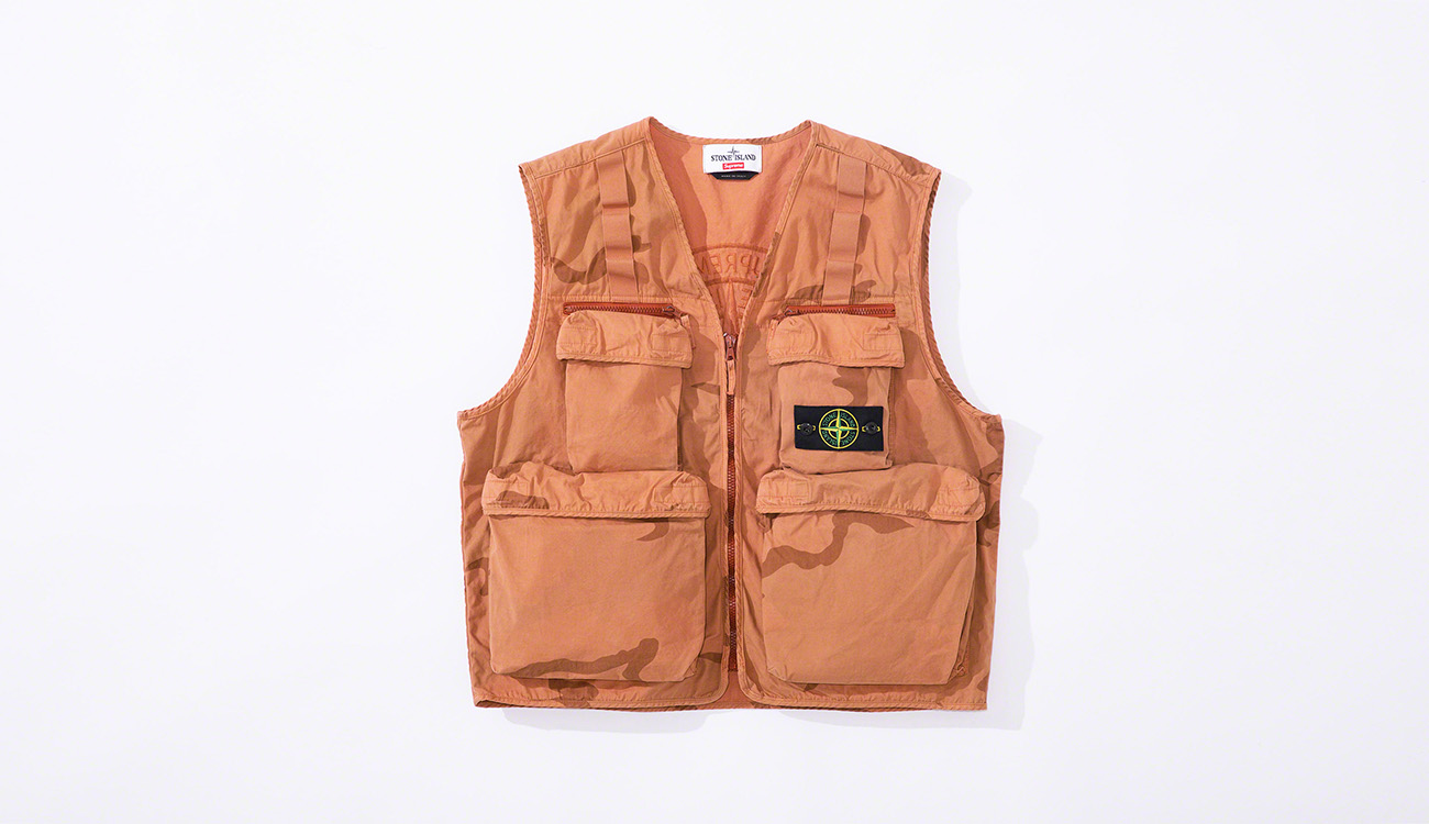 Orange vest in brushed cotton canvas in a camouflage print, with multiple pockets and the Stone Island badge at left chest.