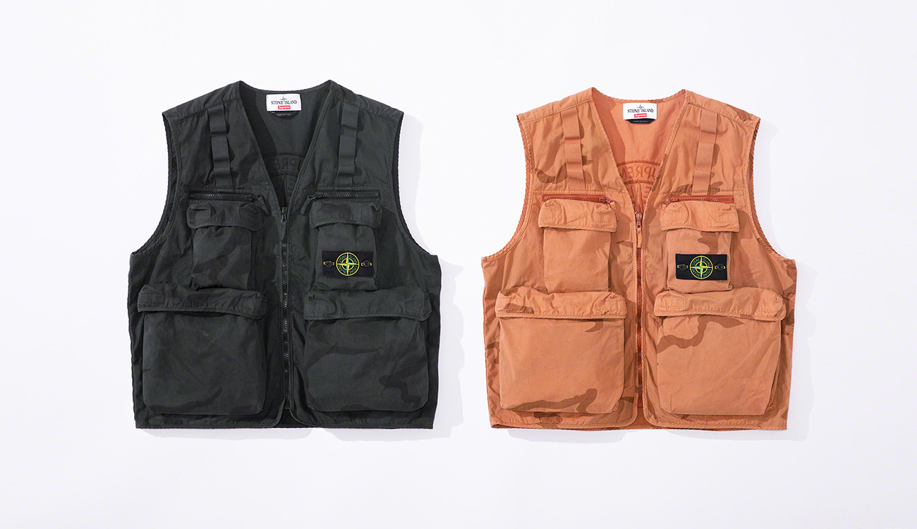 Two vests in brushed cotton canvas with a camouflage print, one in black, one in orange, both with multiple pockets and the Stone Island badge at left chest.