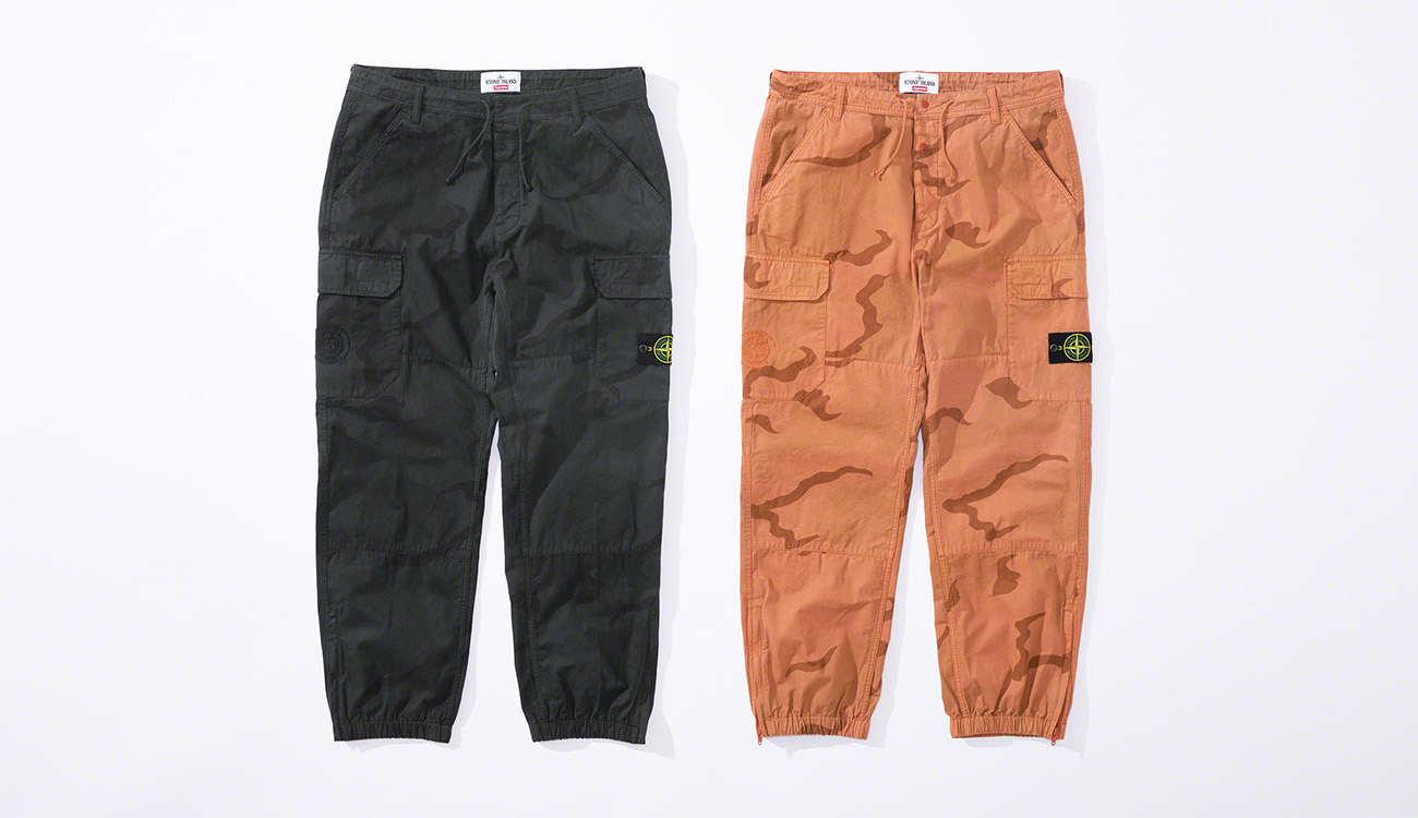One black pair and one orange pair of jogging pants in brushed cotton canvas with a camouflage print and Stone Island badge on the left thigh.