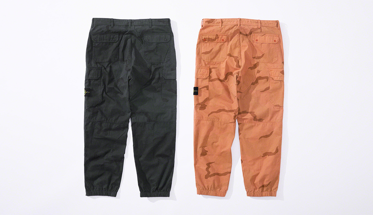 Back view of one black pair and one orange pair of jogging pants in brushed cotton canvas with a camouflage print.