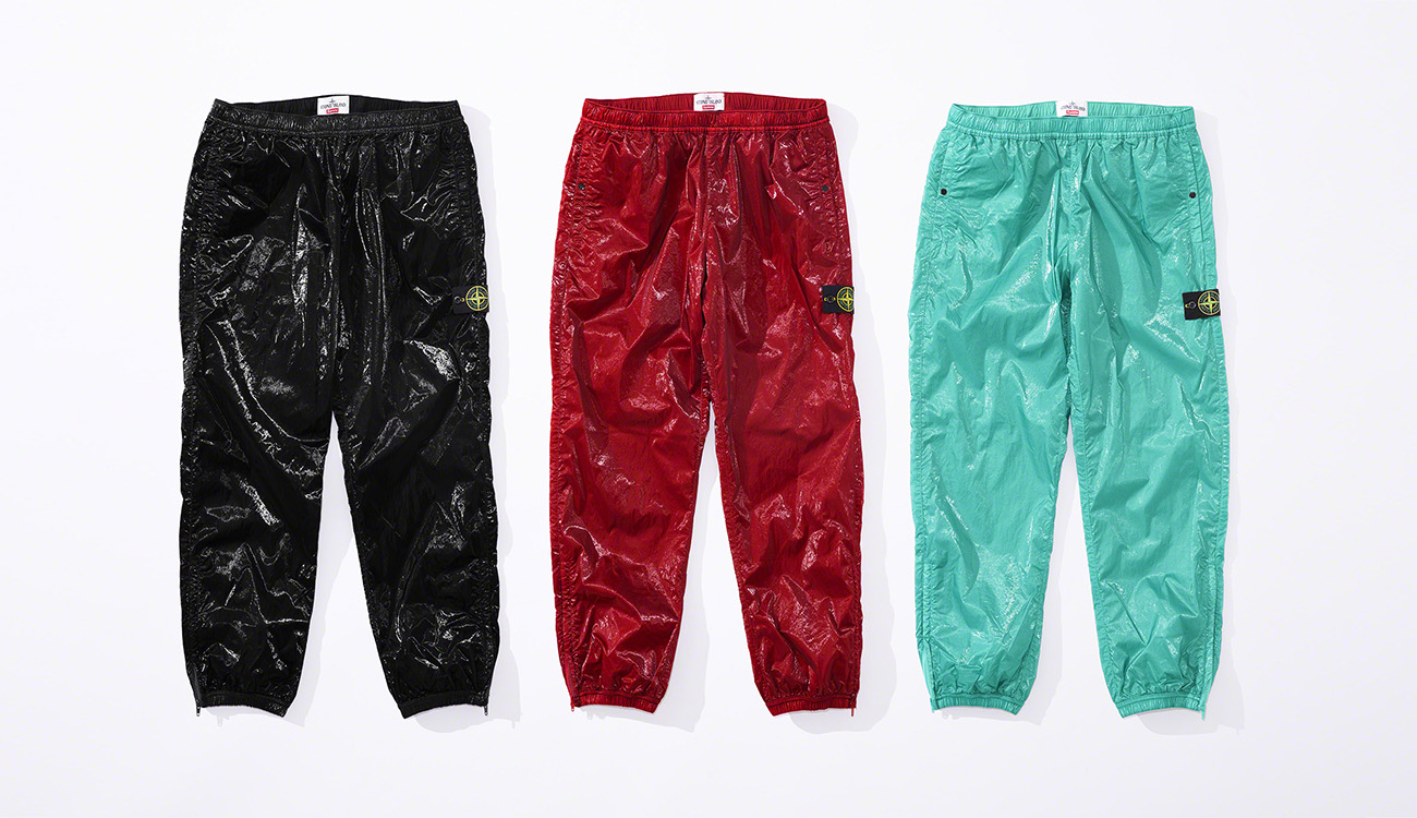 Front view of three pairs of jogging pants in New Silk Light fabric, one black, one red and one aquamarine, all with Stone Island badge on the left thigh.