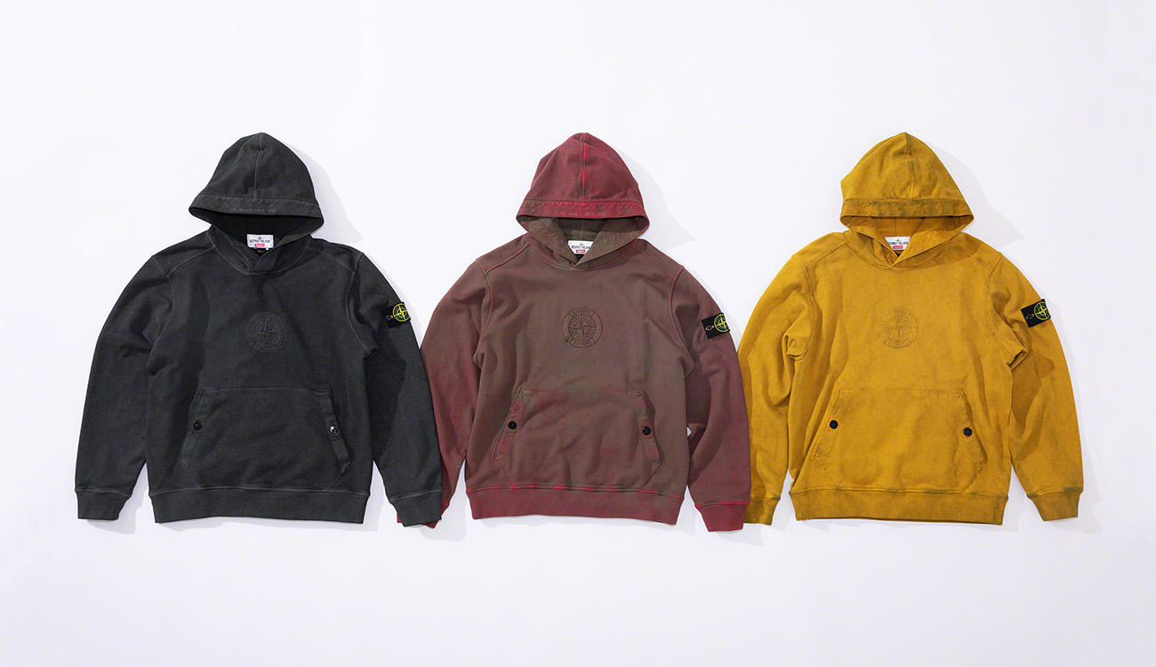 Three hooded sweatshirts, one black, one faded red and one yellow, all with a pouch pocket and the Stone Island Supreme PIN embroidery on the chest.