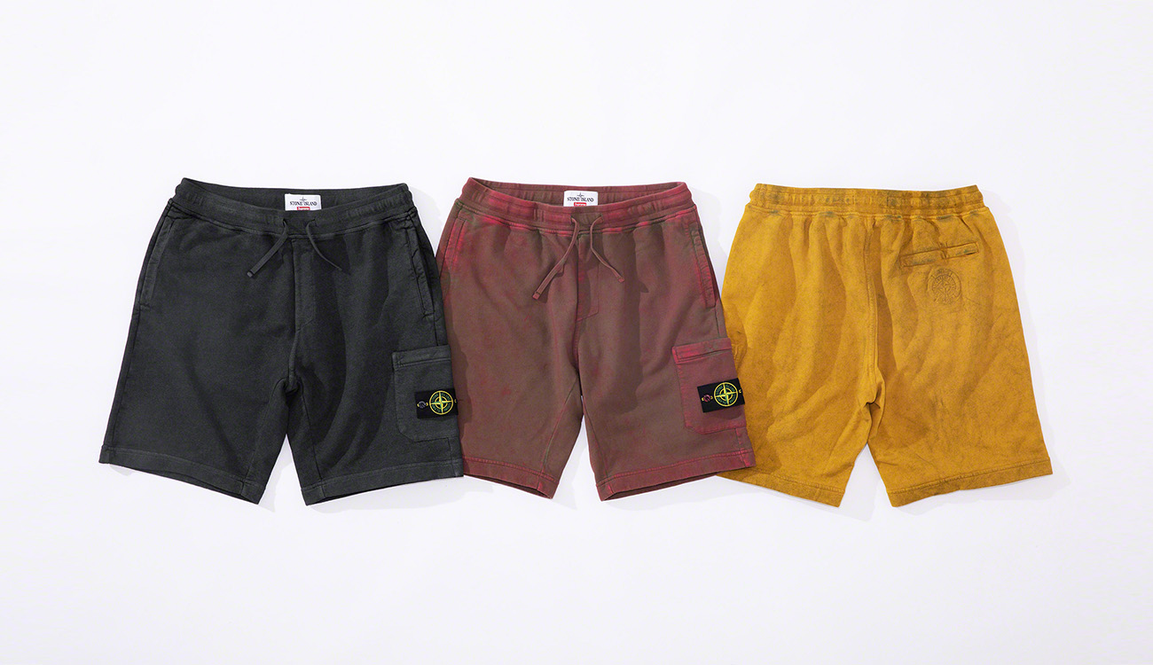 Three pairs of bermuda shorts, one black, one faded red and one yellow.