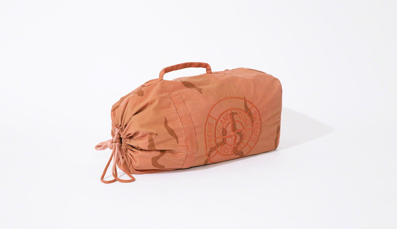 An orange, military shoulder bag with a camouflage print.