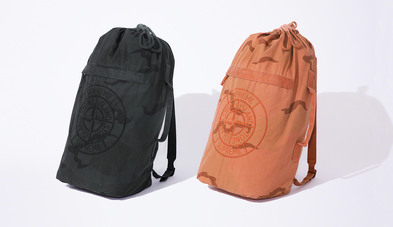 Two military shoulder bags, one black and one orange, both with a camouflage print and the Stone Island Supreme PIN  embroidery.