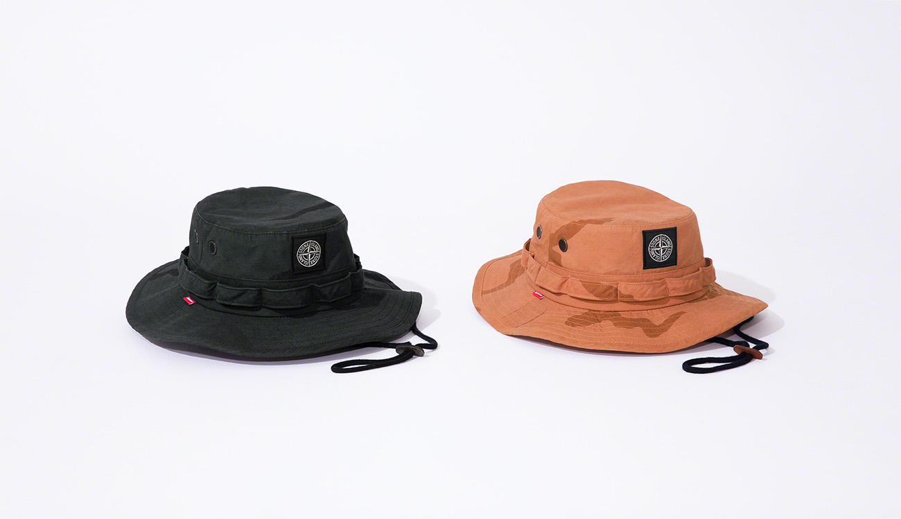 Two boonie hats, one black and one orange, both with a camouflage print and the Stone Island patch.