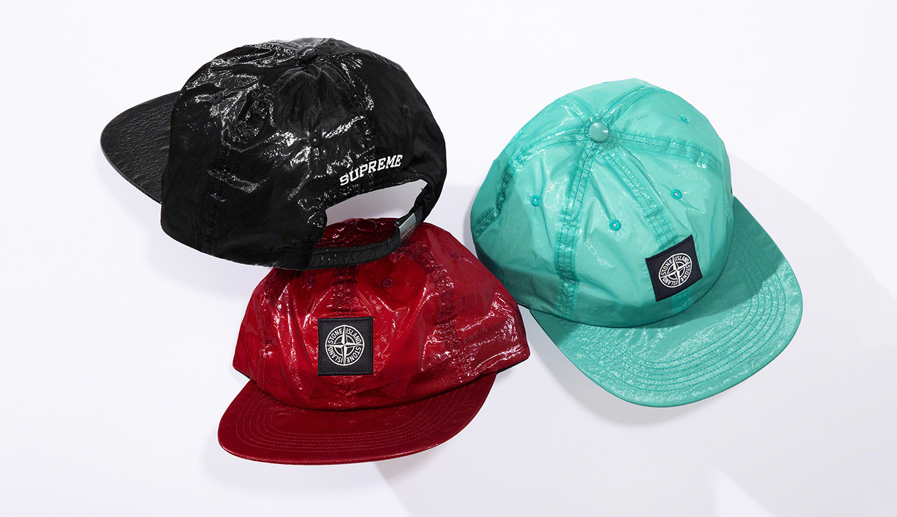 Three caps in New Silk Light fabric, one black, one red and one aquamarine, with the Stone Island patch on the front and Supreme lettering on the back.