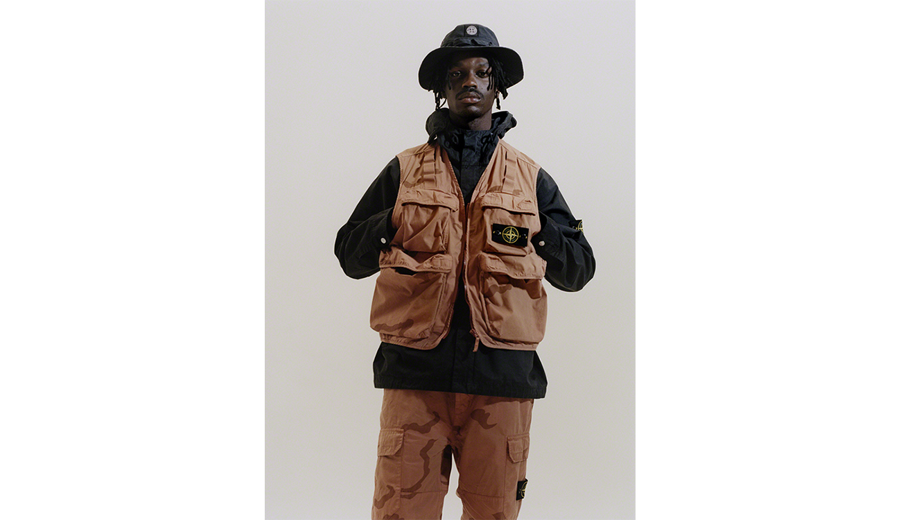 Model wearing an orange vest and orange pants both in brushed cotton canvas with a camouflage print, and a black boonie hat.