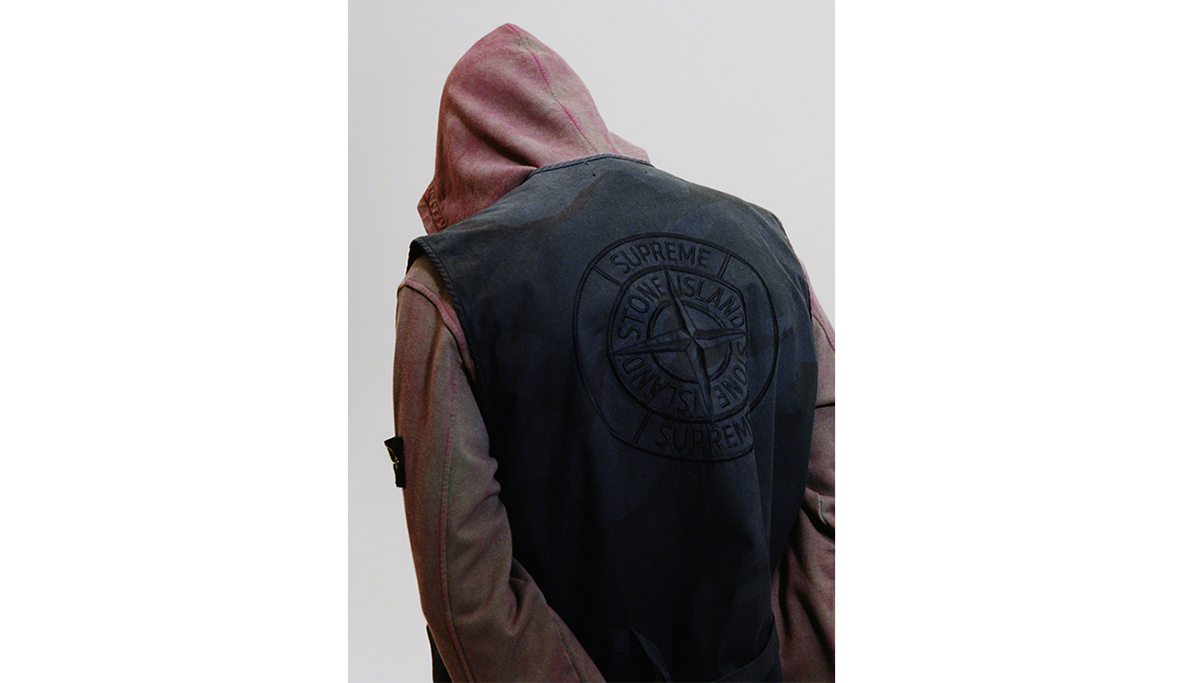 Back view of model wearing a black vest showing the Stone Island Supreme PIN on the back embroidery.