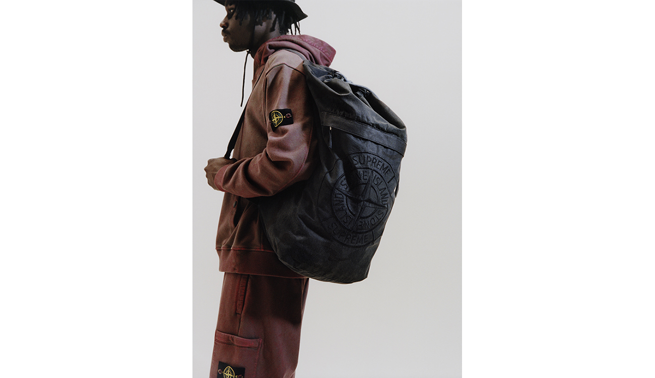 Model wearing a faded red, hooded sweatshirt, matching jogging pants and carrying a black shoulder bag with the Stone Island compass rose logo embroidery.