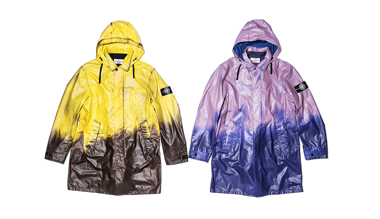 Two trench coats, one brown, one blue in Heat Reactive fabric seen as they respond to heat. The brown turns yellow, the blue turns lilac including the hoods.