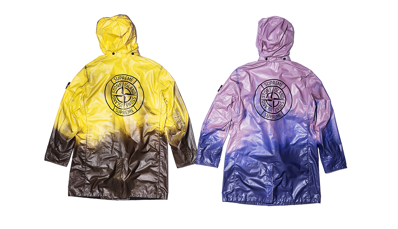 The backs of two trench coats, one yellow, one lilac, in Heat Reactive fabric seen as they respond to heat. The yellow turns brown, the lilac turns blue.