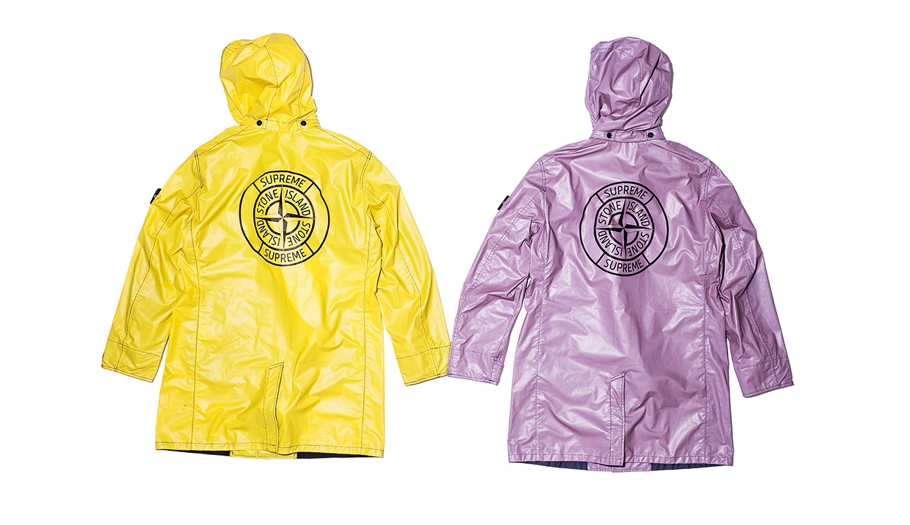 The backs of two trench coats, one yellow, one lilac, in Heat Reactive fabric.