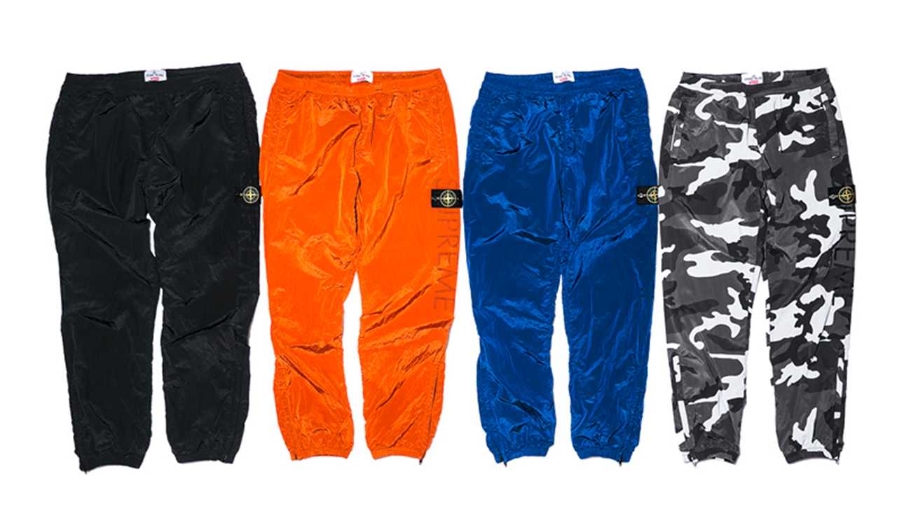 Four trackpants, one black, one orange, one blue and one camouflage print all in Nylon Metal fabric.