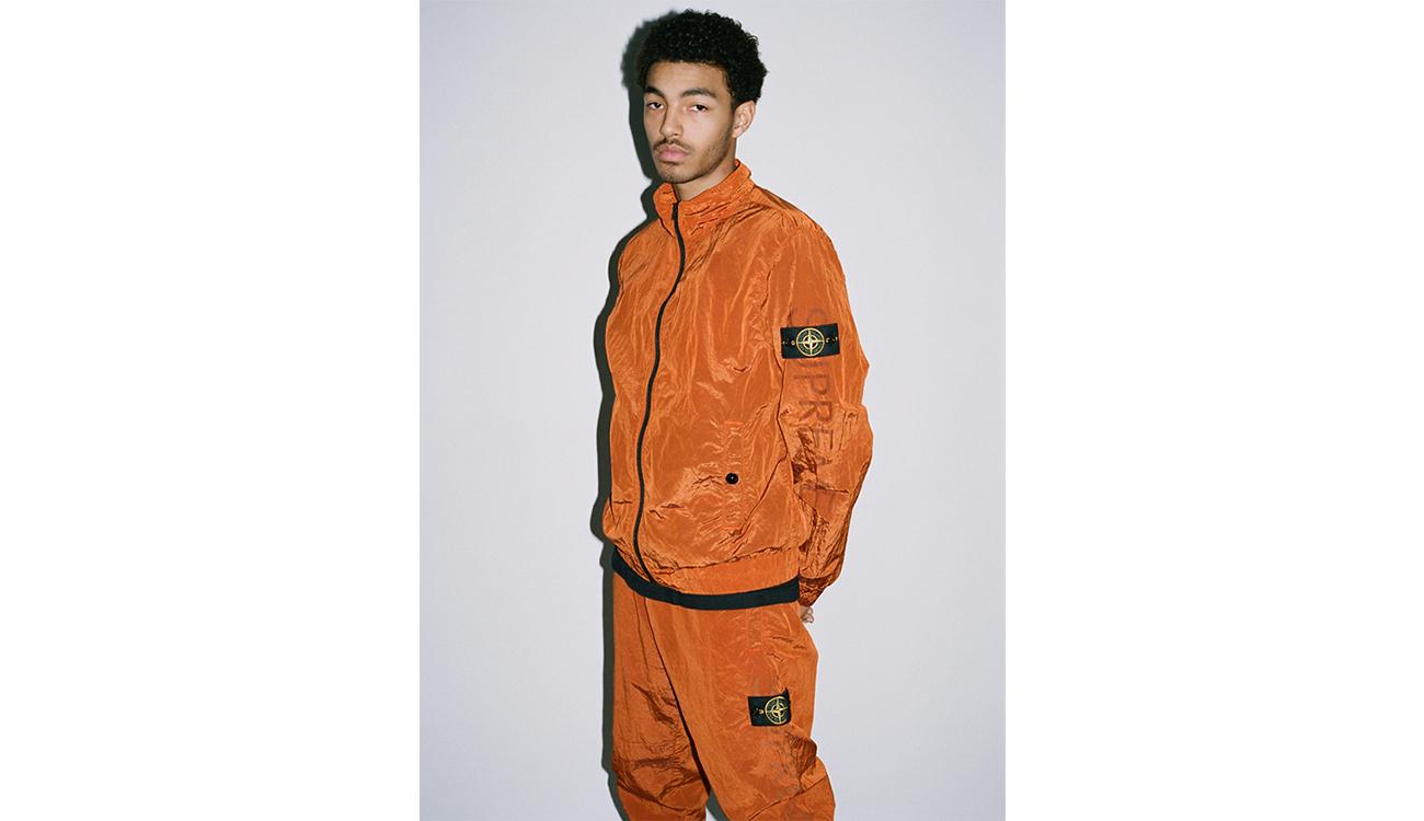 Model wearing orange tracksuit in Nylon Metal fabric.