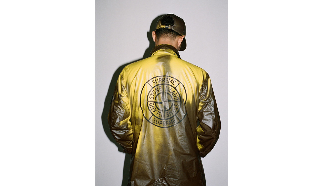 Model showing Supreme Stone Island logo printed on back of yellow trench coat in Heat Reactive fabric.