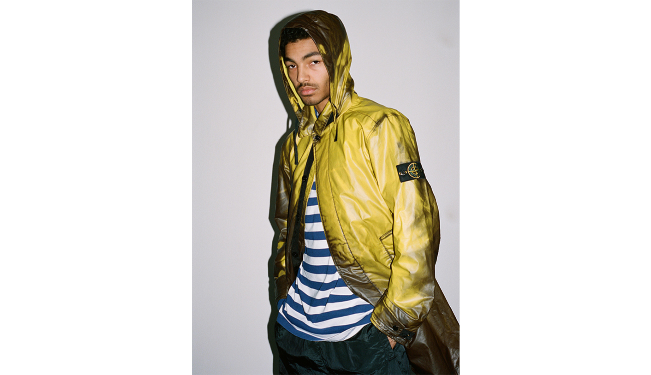 Model wearing yellow trench coat in Heat Reactive fabric.