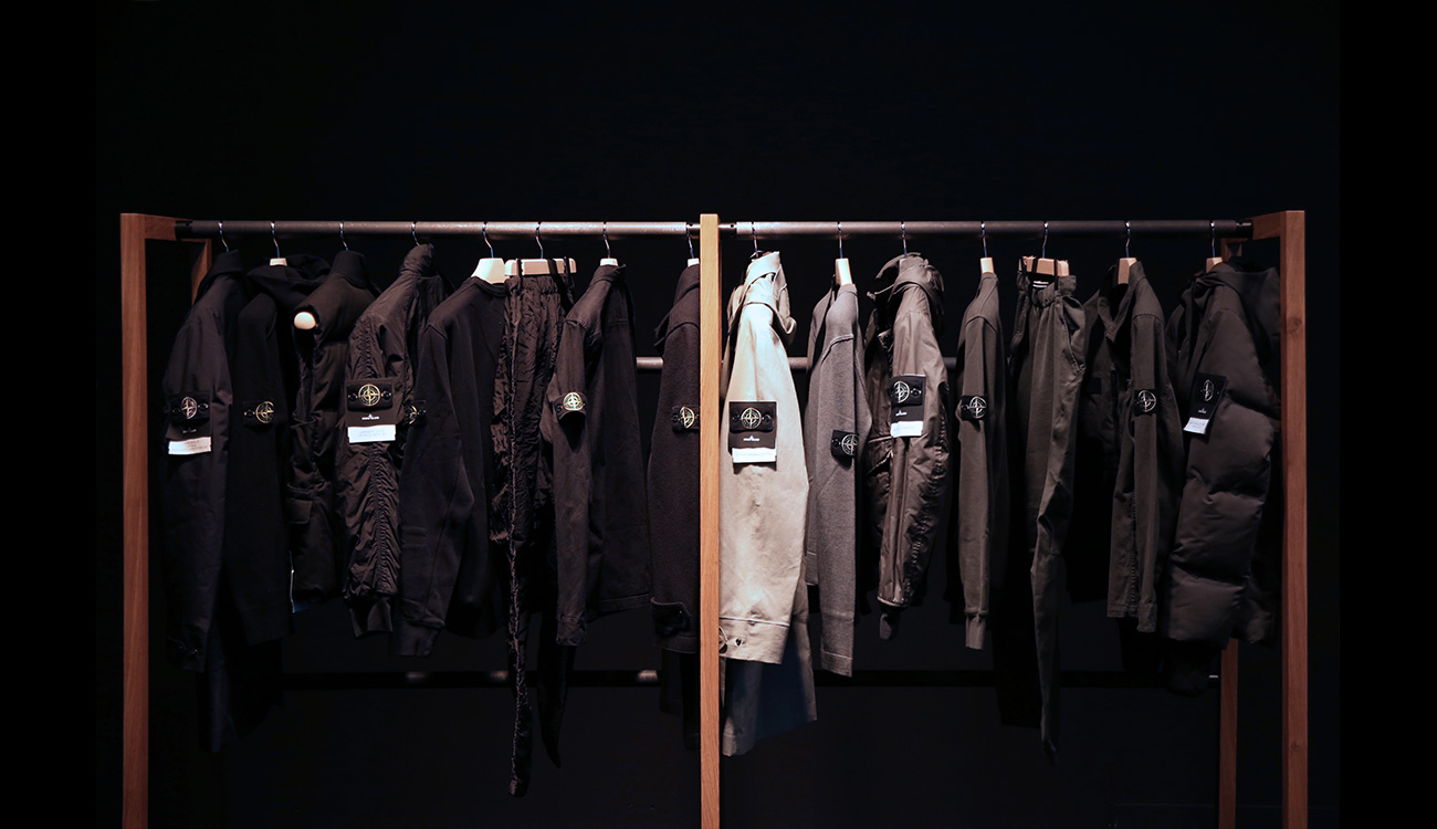 Black and gray jackets and pants hanging from a clothes rack.