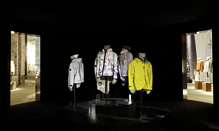 A blacked out room with a group of spot lit mannequins wearing different jackets in white, gray and yellow.