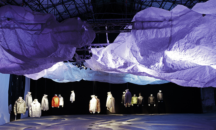 Artistic installation of Stone Island jackets displayed on half body mannequins suspended from steel girders and fabric clouds.