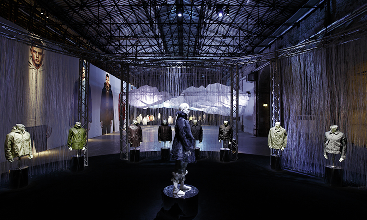 Artistic installation of mannequins in Stone Island jackets in different styles and colors displayed in a dimly lit industrial space with lots of steel girders.