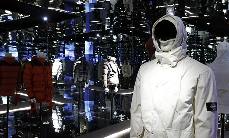 Exhibition of mannequins wearing Stone Island jackets with particular focus on a white jacket displayed with hood and chin strap worn up.