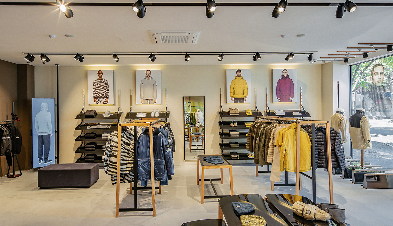 Bright store interior with different colored clothes displayed on clothes racks, shelves and tables.