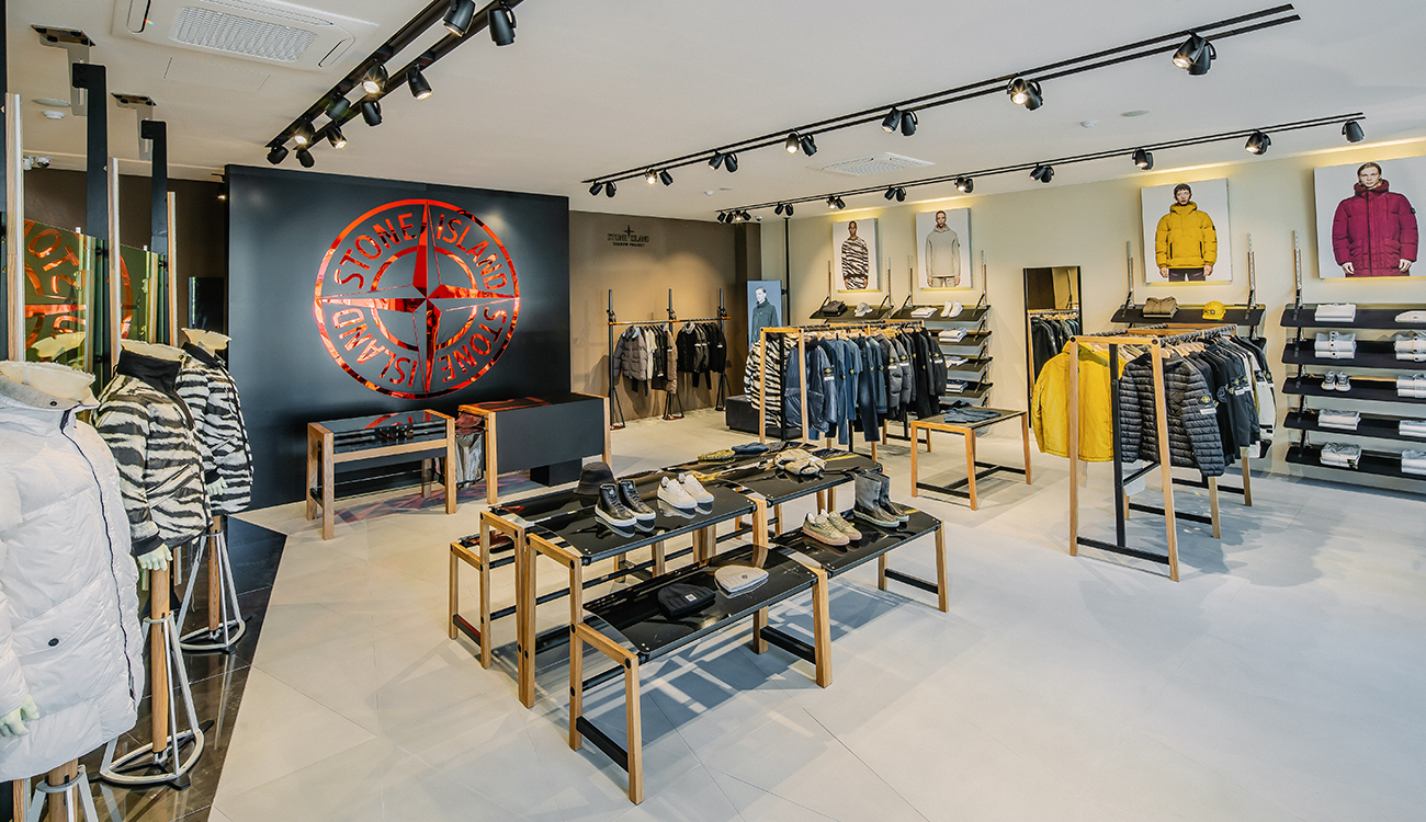Store interior with the red, mirror cut, Stone Island compass logo on wall.