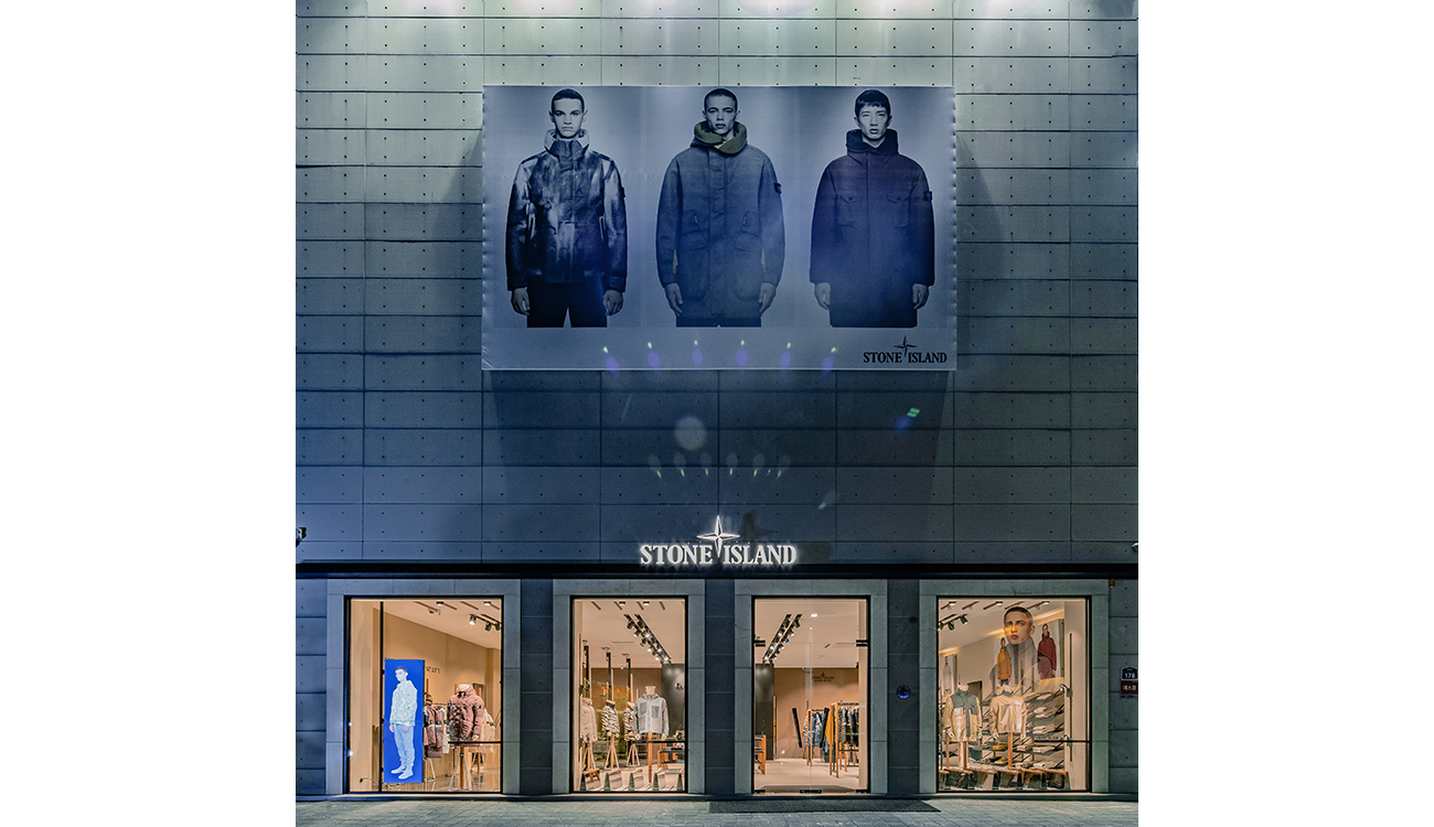 Large billboard poster of three models in Stone Island jackets over store entrance.