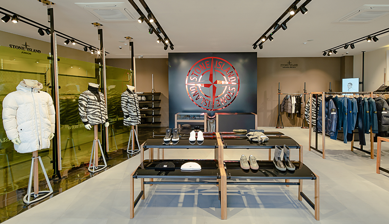 Store interior with yellow glass panels, mannequins in tiger print jackets and the Stone Island compass logo on the back wall.